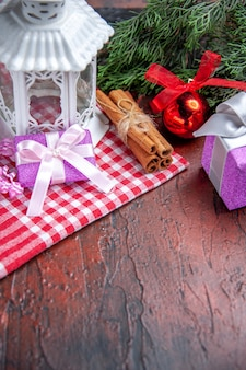 Vue de face cadeaux de noël branches de pin boule de noël jouet lanterne nappe rouge bâtons de cannelle sur fond rouge foncé photo de noël