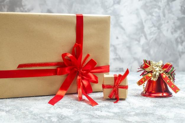 Vue de face des cadeaux de noël emballés avec un arc rouge sur fond blanc