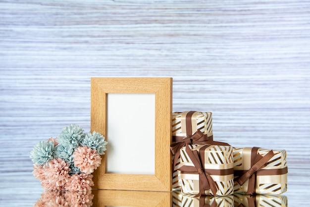 Vue de face des cadeaux de la saint-valentin attachés avec un cadre photo beige de fleurs de ruban reflété sur un miroir
