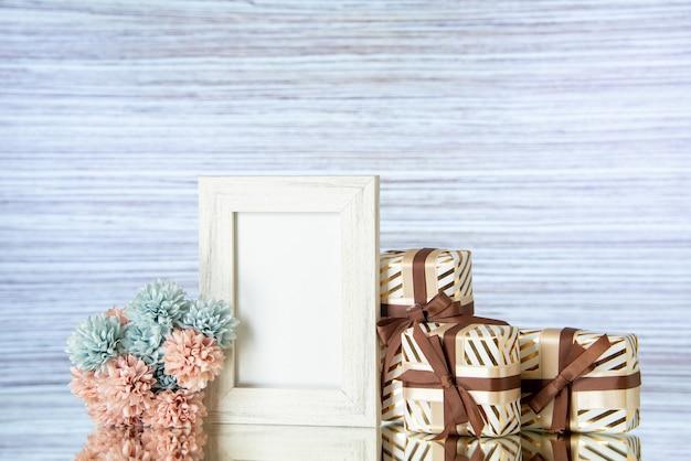 Vue de face des cadeaux de la saint-valentin attachés avec un cadre photo blanc de fleurs de ruban marron réfléchi sur un miroir