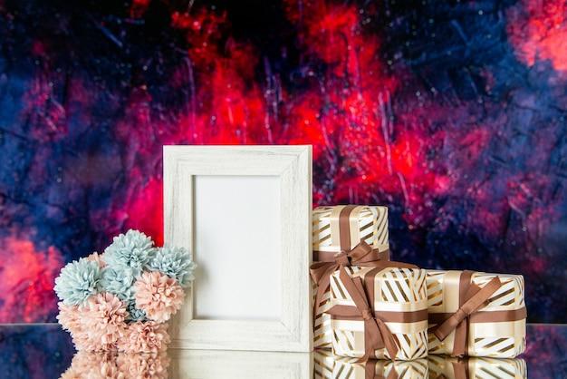Vue de face des cadeaux de la saint-valentin attachés avec un cadre photo blanc de fleurs de ruban réfléchi sur un miroir sur fond abstrait rouge foncé
