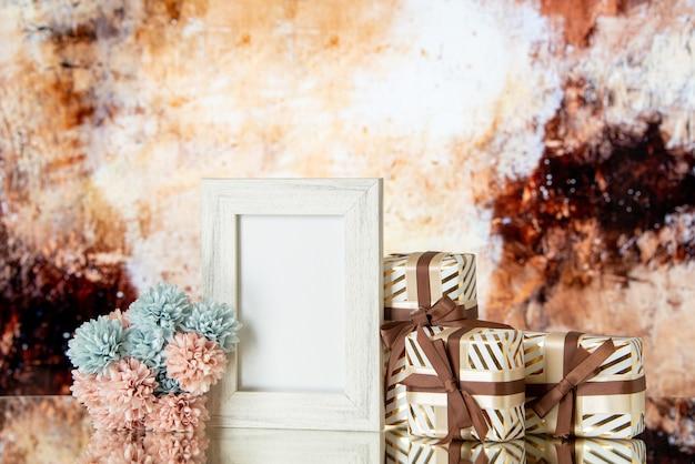 Vue de face des cadeaux de la saint-valentin attachés avec un cadre photo blanc de fleurs de ruban réfléchi sur un miroir sur fond abstrait