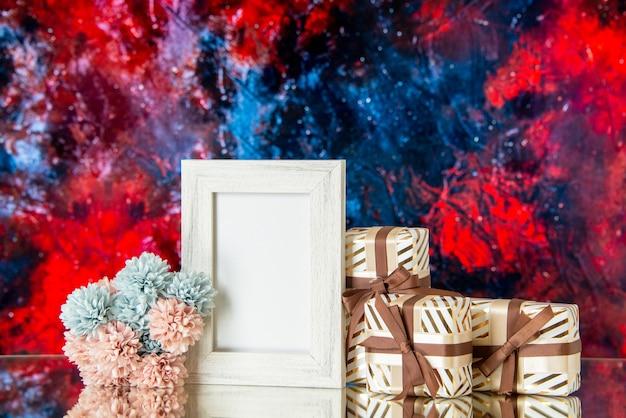 Vue de face des cadeaux de la saint-valentin attachés avec un cadre photo blanc de fleurs de ruban réfléchi sur un miroir sur fond rouge foncé