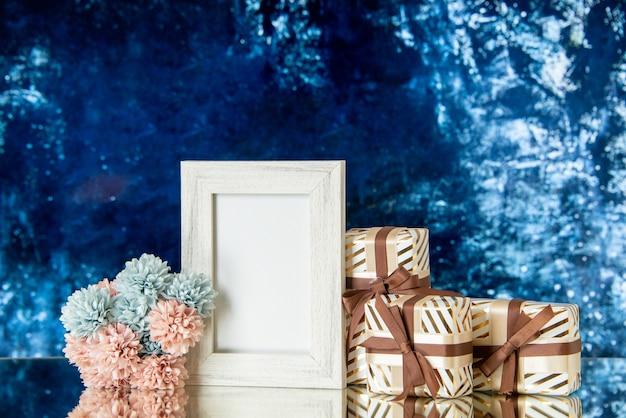 Vue de face des cadeaux de la saint-valentin attachés avec un cadre photo blanc de fleurs de ruban reflété sur un miroir sur fond bleu foncé