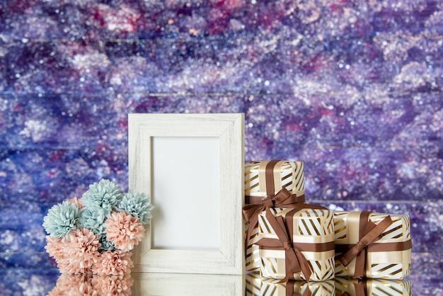 Vue de face cadeaux saint valentin fleurs cadre photo blanc réfléchi sur miroir sur fond aquarelle violet espace libre
