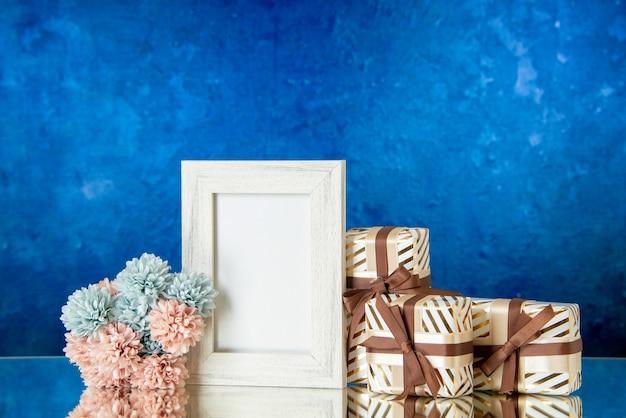 Vue de face cadeaux saint valentin fleurs cadre photo doré réfléchi sur miroir sur fond bleu foncé espace libre