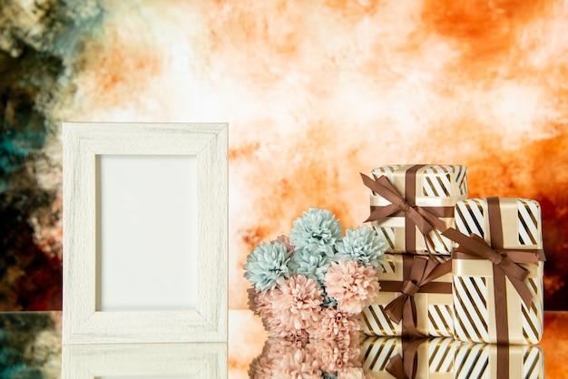 Vue de face des cadeaux de vacances de cadre photo blanc reflétés sur le miroir