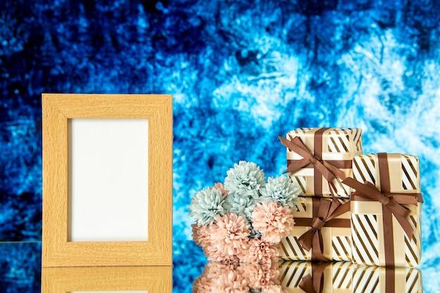 Vue de face des cadeaux de vacances cadre photo vide fleurs sur fond abstrait bleu