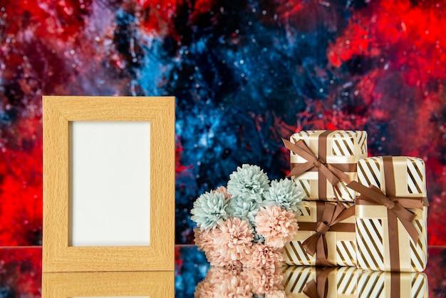 Vue de face des cadeaux de vacances cadre photo vide fleurs sur fond abstrait rouge foncé