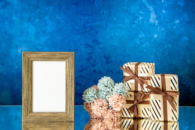 Vue de face des cadeaux de vacances cadre photo vide fleurs sur fond bleu