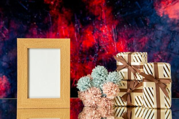 Vue de face des cadeaux de vacances cadre photo vide fleurs sur fond rouge foncé