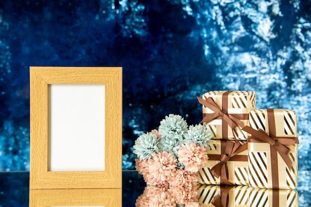Vue de face cadeaux de vacances cadre photo vide fleurs reflétées sur miroir sur fond bleu foncé