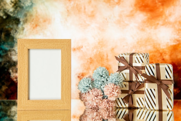Vue de face des cadeaux de vacances des fleurs de cadre photo vides reflétées sur le lieu de copie du miroir