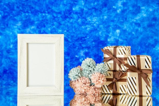 Vue de face des cadeaux de vacances des fleurs de cadre photo vides reflétées sur un miroir avec un arrière-plan flou bleu