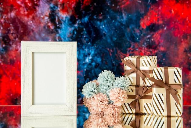 Vue de face des cadeaux de vacances des fleurs de cadre photo vides reflétées sur un miroir avec un fond abstrait rouge foncé