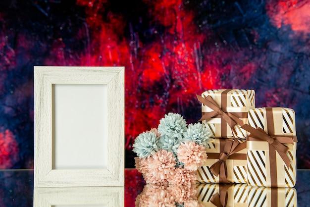 Vue de face des cadeaux de vacances des fleurs de cadre photo vides reflétées sur un miroir avec un fond rouge foncé
