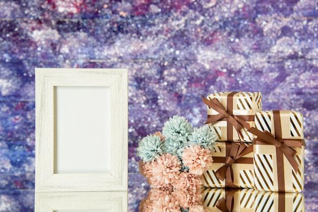 Vue de face cadre photo blanc cadeaux de vacances fleurs reflétées sur miroir avec un fond aquarelle violet