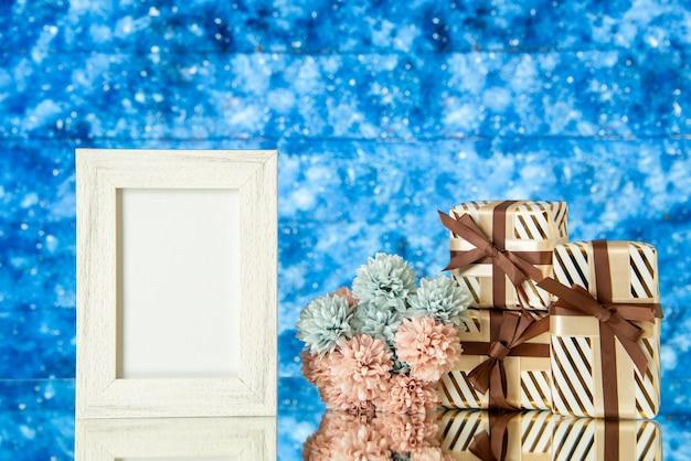 Vue de face cadre photo blanc cadeaux de vacances fleurs reflétées sur miroir avec un fond d'espace bleu
