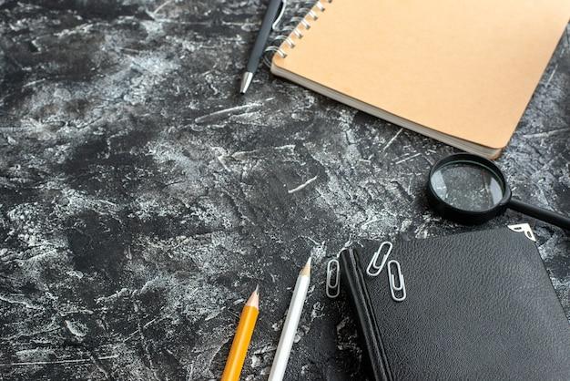 Vue de face cahier noir avec crayons et boussole sur fond gris couleur cahier de bord stylo collège bloc-notes leçon école