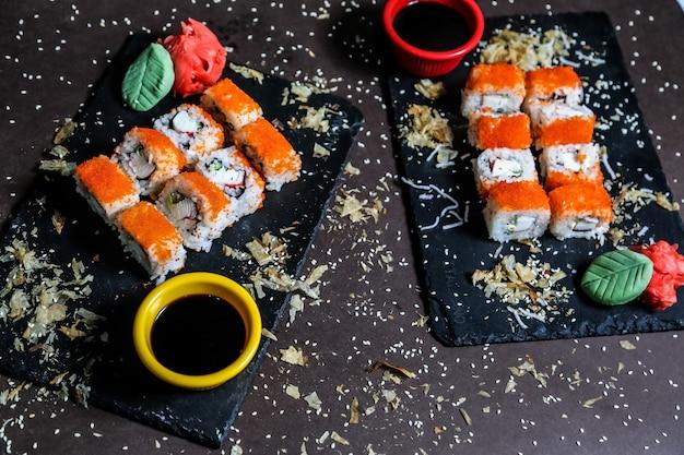 Vue de face california rolls avec sauce soja, gingembre et wasabi sur ardoises noires