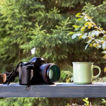 Vue de face de la caméra et tasse de café dans la nature