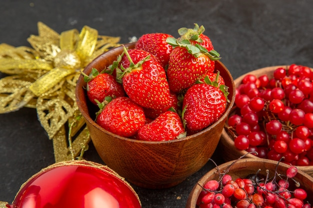 Vue de face des canneberges rouges fraîches avec d'autres fruits autour des jouets de noël sur la baie de fruits de vacances de noël de couleur de fond sombre