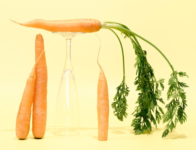 Vue de face des carottes avec verre vide