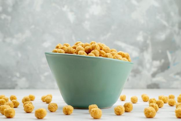 Vue de face des céréales crues de couleur jaune à l'intérieur de la plaque verte sur blanc, petit déjeuner céréales cornflakes santé