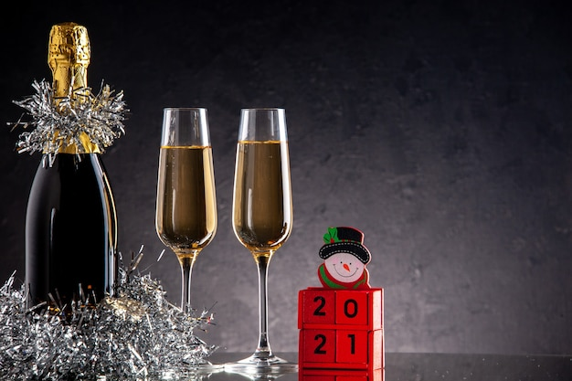 Vue de face champagne en bouteille et verres blocs de bois sur une surface sombre