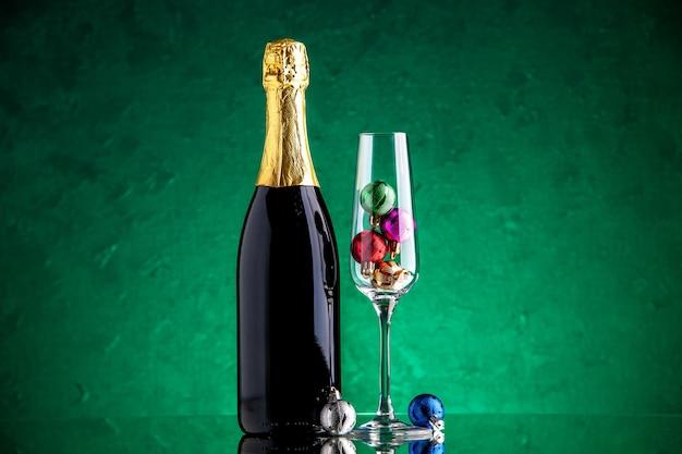 Vue de face champagne petites boules de noël dans un verre à vin sur une surface verte