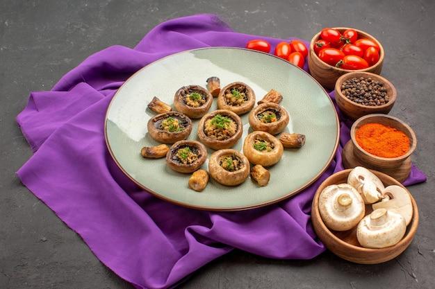 Vue de face des champignons cuits à l'intérieur de la plaque avec des assaisonnements sur un plat de tissu violet repas cuisson dîner aux champignons