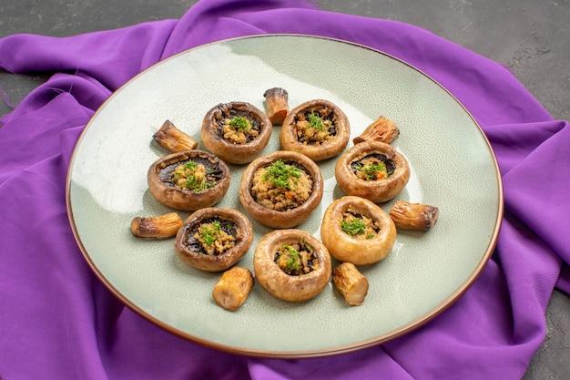 Vue de face champignons cuits à l'intérieur de la plaque sur tissu violet et sur fond sombre plat repas cuisson champignons dîner