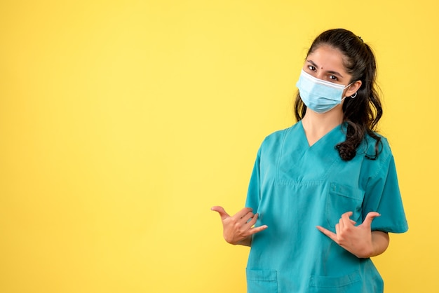 Vue de face charmante femme médecin avec masque médical debout sur fond jaune