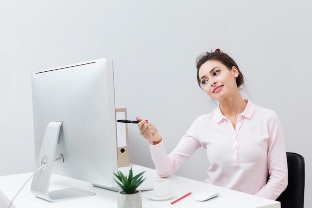 Vue de face de la charmante femme pointant le stylo à l'ordinateur