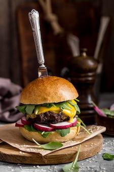 Vue de face cheeseburger sur planche à découper avec couteau