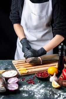 Vue de face chef avec des gants noirs coupant la tête de poisson sur une planche à découper moulin à poivre bol de farine graines de grenade dans un bol sur la table de la cuisine