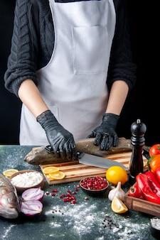 Vue de face chef avec des gants noirs hacher du poisson cru sur planche de bois moulin à poivre bol de farine graines de grenade dans un bol sur la table de la cuisine