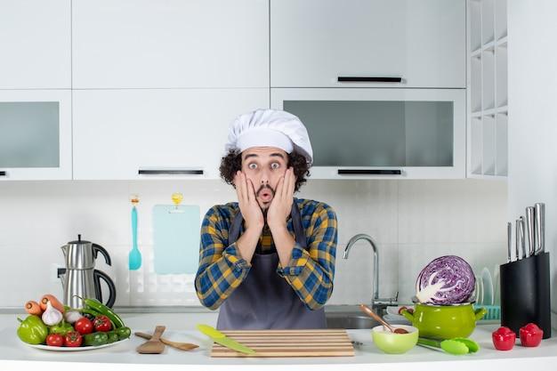 Vue de face d'un chef masculin choqué avec des légumes frais et cuisine avec des ustensiles de cuisine et posant dans la cuisine blanche