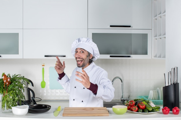 Vue de face chef masculin exalté qui sort la langue debout derrière la table de la cuisine