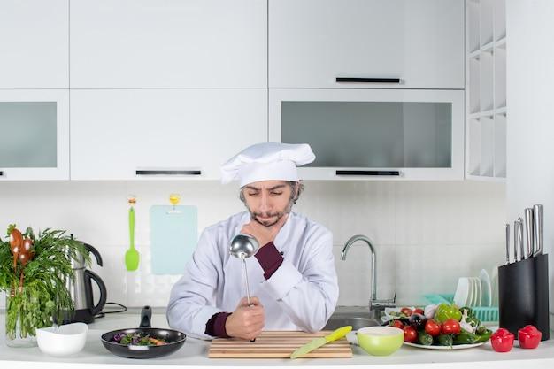 Vue de face chef masculin réfléchi en uniforme brandissant un scoop dans la cuisine