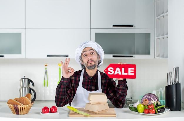 Vue de face d'un chef masculin satisfait en uniforme brandissant un panneau de vente rouge faisant des gestes ok dans une cuisine moderne