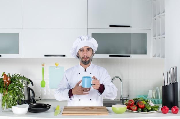 Vue de face chef masculin sérieux en chapeau de cuisinier tenant une tasse debout derrière la table de la cuisine