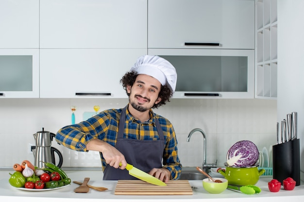 Vue de face d'un chef masculin souriant avec des légumes frais et cuisinant avec des ustensiles de cuisine et coupant quelque chose dans la cuisine blanche