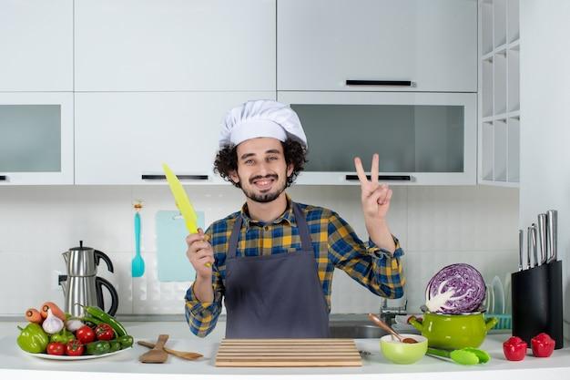 Vue de face d'un chef masculin souriant avec des légumes frais et cuisine avec des ustensiles de cuisine et faisant un geste de victoire tenant un couteau dans la cuisine blanche