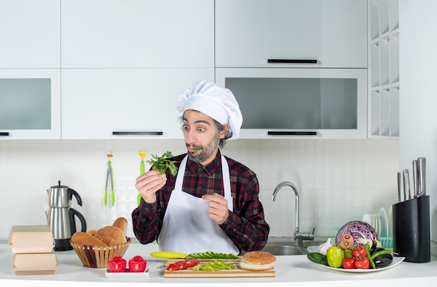 Vue de face chef masculin tenant des verts dans la cuisine