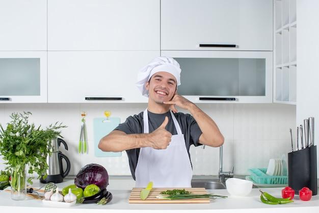 Vue de face chef masculin en uniforme donnant les pouces vers le haut derrière la table de la cuisine