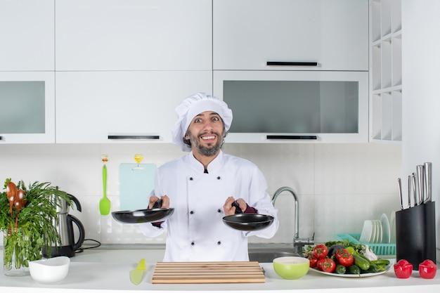 Vue de face chef masculin en uniforme tenant des casseroles de différentes tailles dans une cuisine moderne