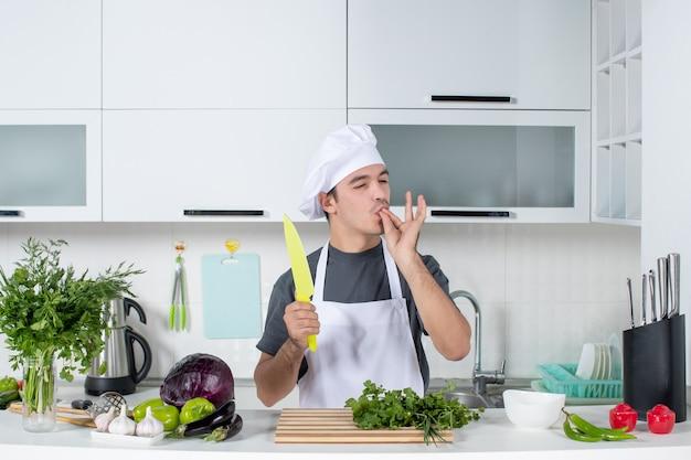 Vue de face chef masculin en uniforme tenant un couteau dans la cuisine faisant un baiser de chef