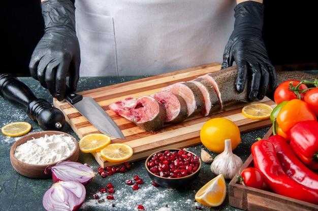 Vue de face chef tenant des tranches de poisson cru et un couteau sur une planche à découper des légumes sur une planche de service en bois sur une table de cuisine