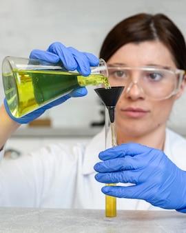 Vue de face de la chercheuse avec des lunettes de sécurité tenant des tubes à essai